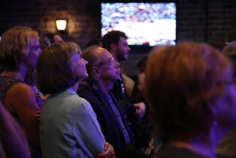 Sally Greene, the democratic candidate for Board of Commissioners, looks on to voting updates at Orange County's Democratic Party's election party at Might as Well in Chapel Hill.