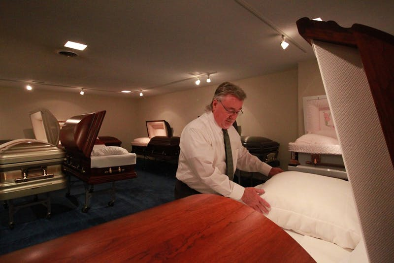 Art Sellers, director of Walker's Funeral Home, explains the casket selection process in the casket selection room of the funeral home. Families select caskets, urns and burial vaults here.