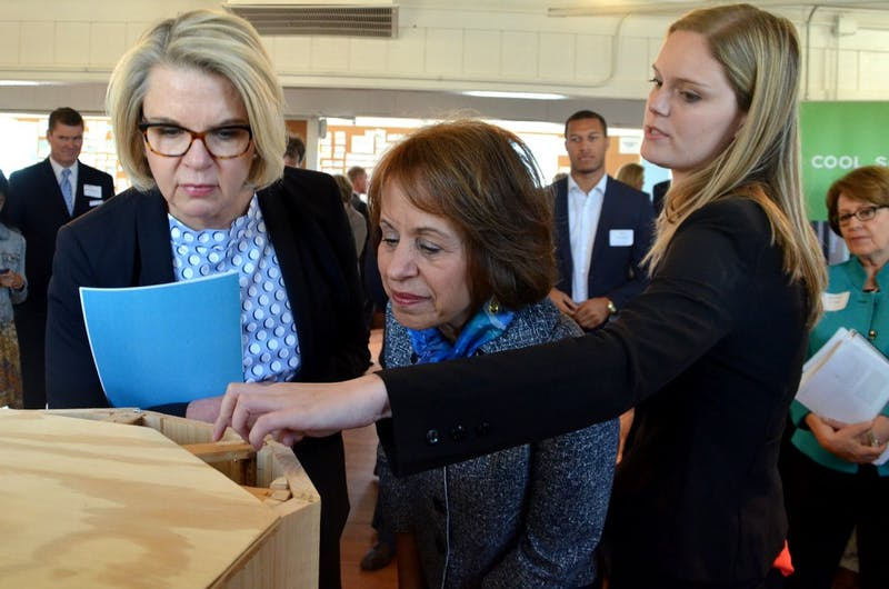 Alsey Davidson shows UNC System President Margaret Spellings and Chancellor Carol Folt how Honey Halo's beehive design can save the lives of honeybees.
