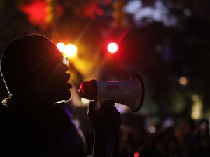 A UNC student speaks to a crowd on Franklin Street in front of the UNC-system president's house to speak on behalf of the removal of Silent Sam in August 2017.