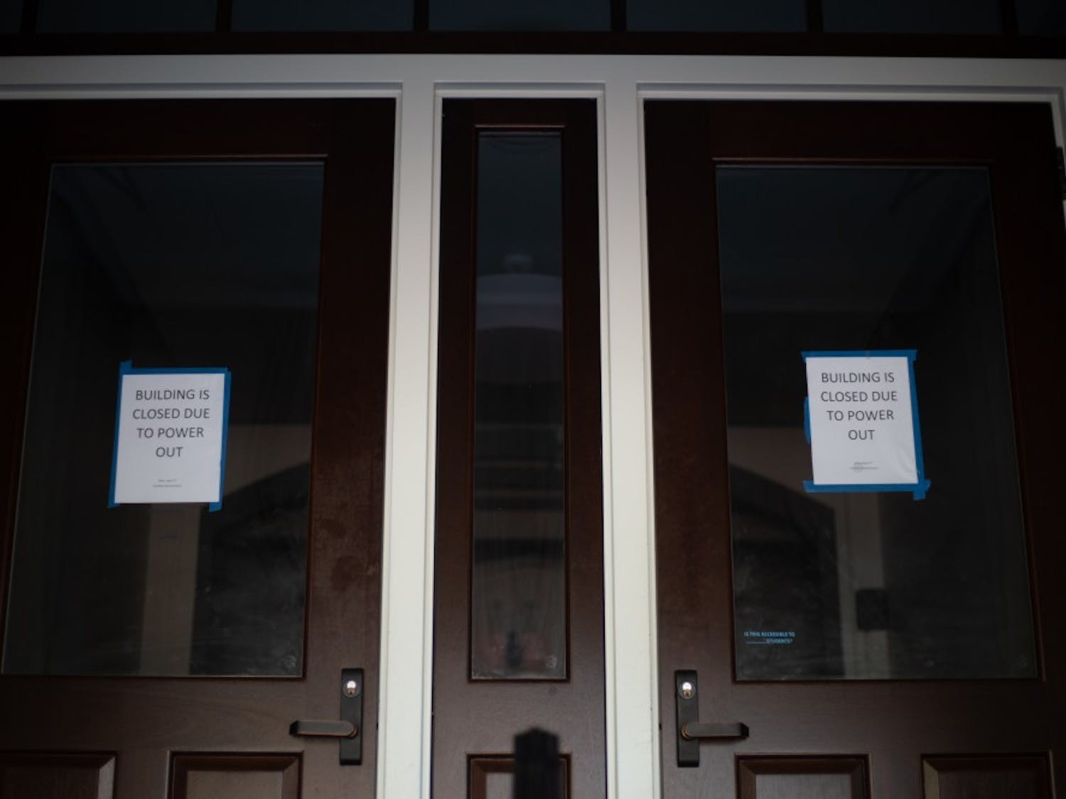 Signs on the locked front doors of Phillips Hall warn students that the power is out on April 3, 2019.
