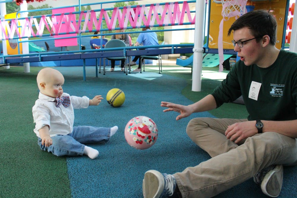 <p>A Carolina for the Kids member plays with a child in UNC Hospitals. Photo courtesy Carolina for the Kids.</p>