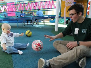 A Carolina for the Kids member plays with a child in UNC Hospitals. Photo courtesy Carolina for the Kids.