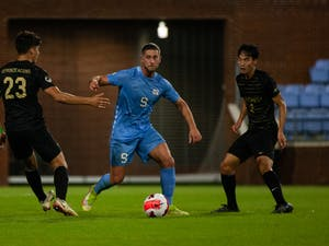 Fifth year forward Santiago Herrera (9) fends off the other team in the Oct. 8 game against Wake Forest. UNC lost 2-1.