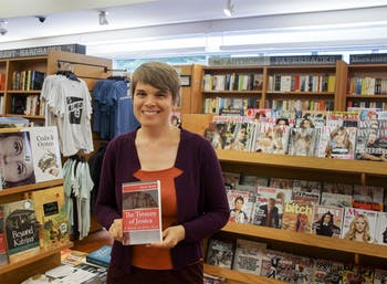 "Erin Ryan, a graduate student in the School of Information and Library Sciences, poses with her book ""The Tyranny of Jessica."""