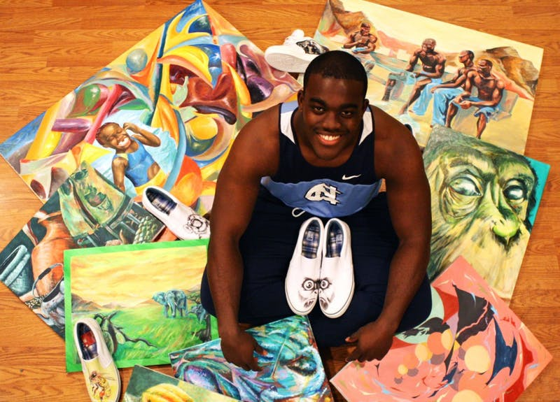 North Carolina track and field athlete Kwabena Keene with some of his best work. The junior is UNC's leader in shot-put and discus throwing, but has a passion for painting in his free time.  In addition to canvas work, Keene also paints custom shoes for his small business, Kwopuni Designs.