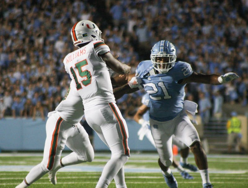 UNC linebacker Chazz Surratt, number 21, is pulled by Miami players on Saturday, Sept. 7, 2019. UNC beat Miami 28-25.