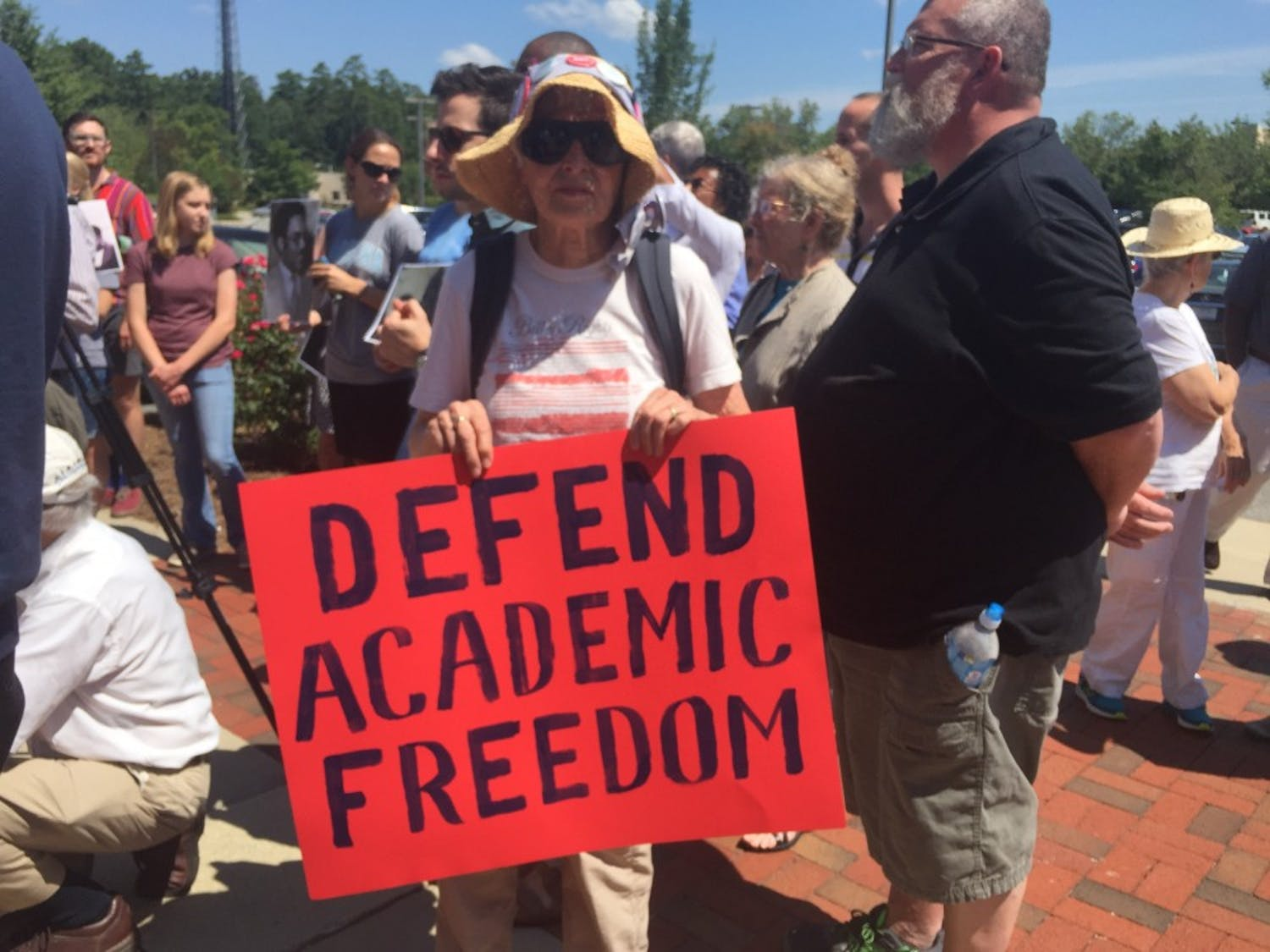 """Margaret Misch, community member and protester, holds a sign reading """"Defend Academic Freedom."""" She said she's been supporting this cause for years."""