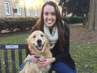 Holden the Golden poses with his owner, UNC senior Caroline Bowers. Holden is in the process of completing an 11 item UNC bucket list and has one semester left.