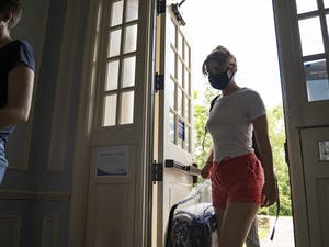 Sophomore Tamsin Engel brings a suitcase into Kenan Residence Hall for move-in on Wednesday, Aug. 5, 2020.