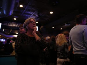 A woman looks on to voting updates at Orange County's Democratic Party's election party at Might as Well in Chapel Hill.