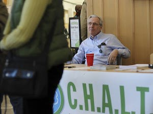 Chapel Hill Alliance for a Livable Town (CHALT) member Don Evans sits behind the organization's informational booth in CH Public Library during their public forum meeting on Sunday.