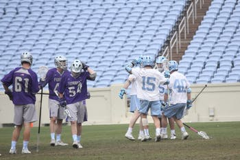 The North Carolina men's lacrosse team celebrates its 15-14 overtime win against Furman on Feb. 10 in Kenan Stadium.