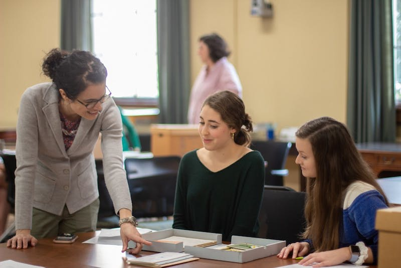 Emily Orland, a first-year history and journalism double major, and Brynn Garner, a junior environmental science and history double major, are instructed by Professor Katherine Turk in Wilson Library on Thursday, Jan. 16, 2020.