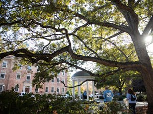 Campus-goers approach the Old Well and South Building on Saturday, Nov. 2, 2019.