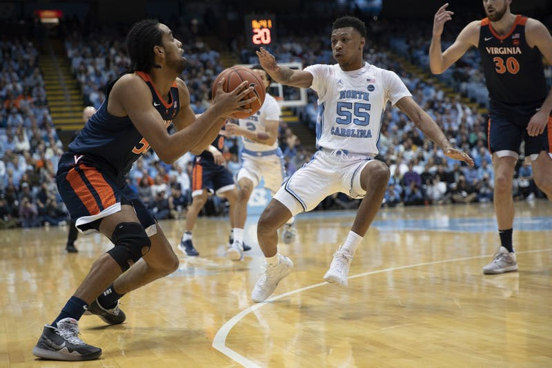 UNC graduate guard Christian Keeling (55) defends Virginia junior guard Tomas Woldetensae (53) on Saturday, Feb. 15, 2020 in the Smith Center. UNC lost to Virginia 64-62.