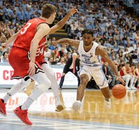 First-year guard Coby White (2) dribbles past Davison players Carter Collins (24) and Jon Axel Gudmundsson (3) before going for a layup at the Smith Center on Saturday. UNC won 82-60.
