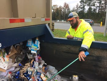 Willliam Coffey removes materials from a recycling bin that contaminate the stream.
