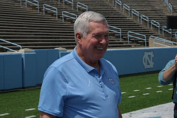 Mack Brown speaks to the press on the field of Kenan Stadium following a conference regarding the upcoming football season.