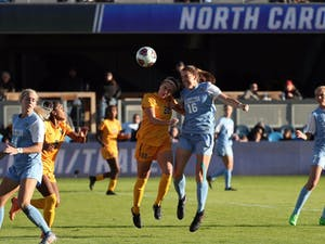 Sophomore defender Julia Ashley (16)goes up for a header againstWest Virginia on Friday. The Tar Heels fell 1-0 in the NCAA semifinal.