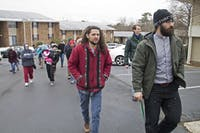 Rev. Nathan Hollister (right) leads protesters into the Estes Park Apartment leasing office Saturday morning to deliver a letter about the complex's water rates rising.