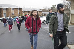 Rev. Nathan Hollister (right) leads protesters into the Estes Park Apartment leasing office on Saturday.