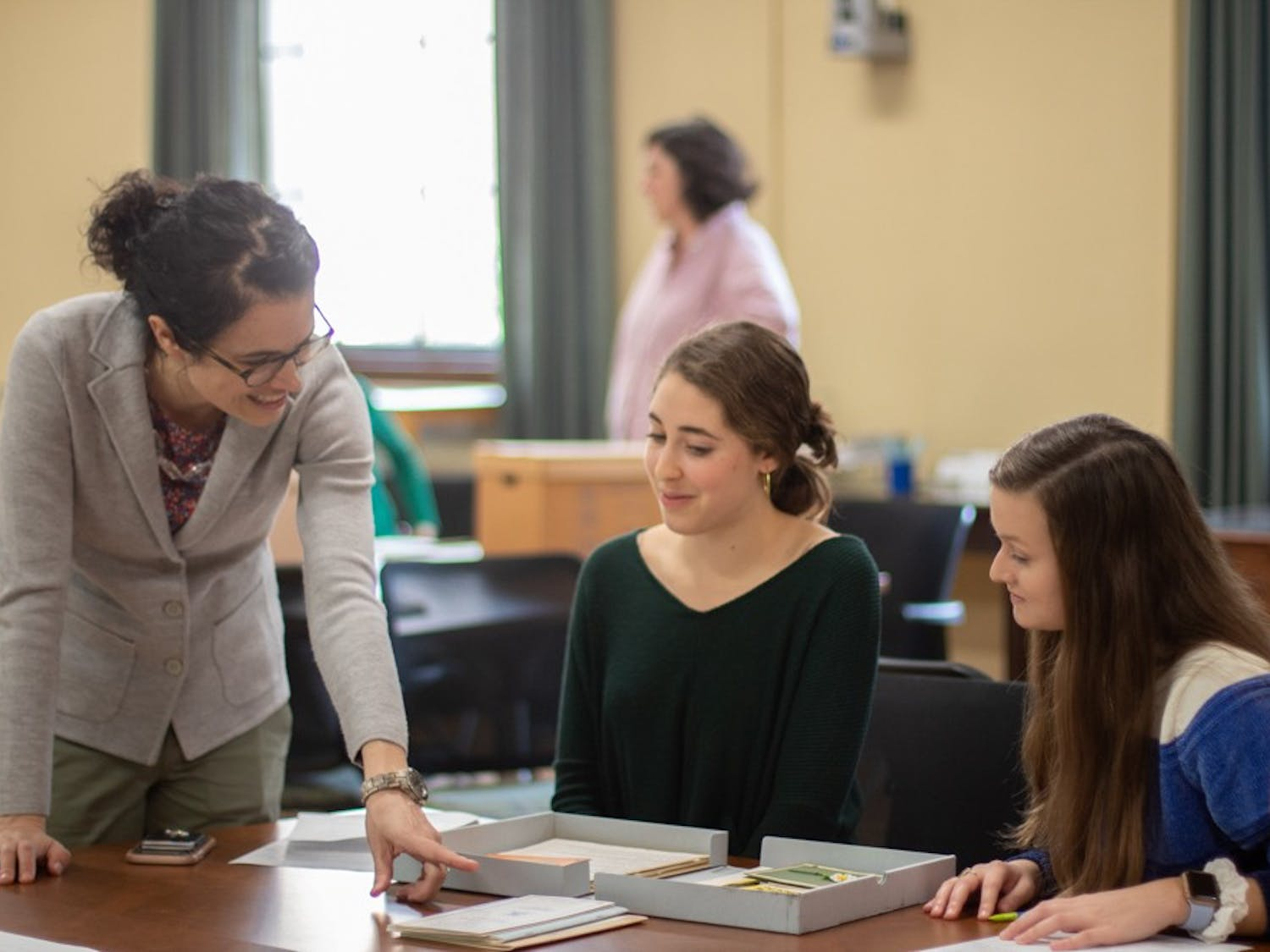 Emily Orland, a first-year history and journalism double major, and Brynn Garner, a junior environmental science and history double major, are instructed by Professor Katherine Turk in Wilson Library on Thursday, Jan. 16, 2020. Photo courtesy of Johnny Andrews.