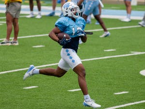 Graduate student transfer running back Ty Chandler (19), runs with the ball at the football practice on Saturday Mar. 27, 2021 at Kenan Stadium.