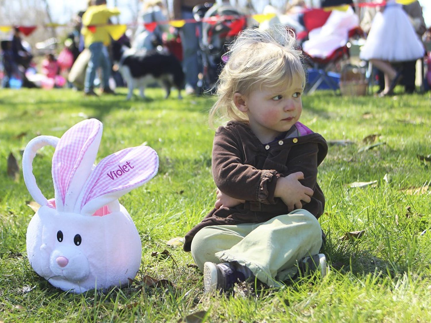 Violet Strickland of Hillsborough sits with her egg basket after the conclusion of Saturday's egg hunt at River Park in Hillsborough. She found one egg.