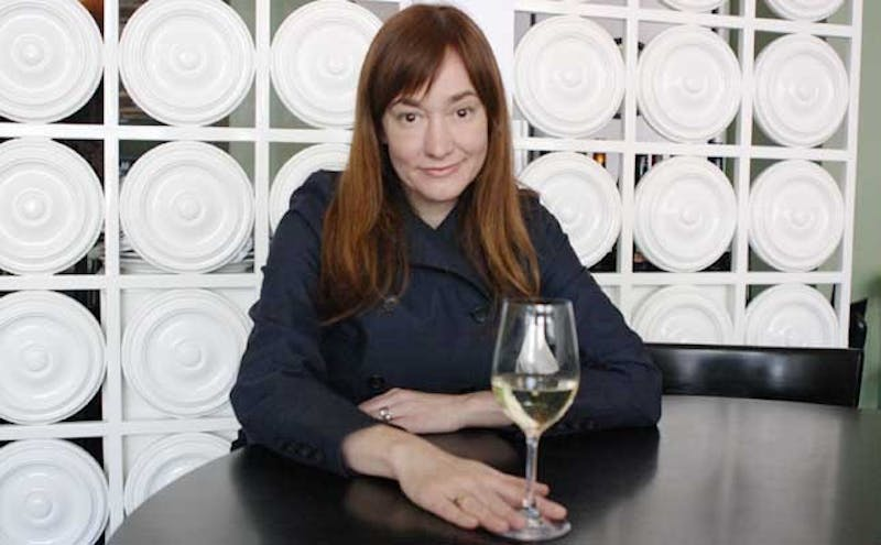 Andrea Reusing, a chef at Lantern, sits at a table in her restaurant.  Reusing is a finalist for a James Beard award for best chef in the Southeast region.  Lantern's dishes mix Asian flavors with North Carolina ingredients.