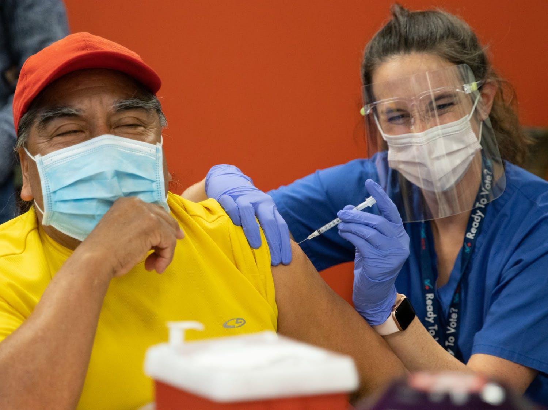 Rocendo Rosas, an immigrant originally from Oaxaca, Mexico, laughs as he receives a COVID-19 vaccine at La Semilla's vaccination event, Feb. 20, 2021.