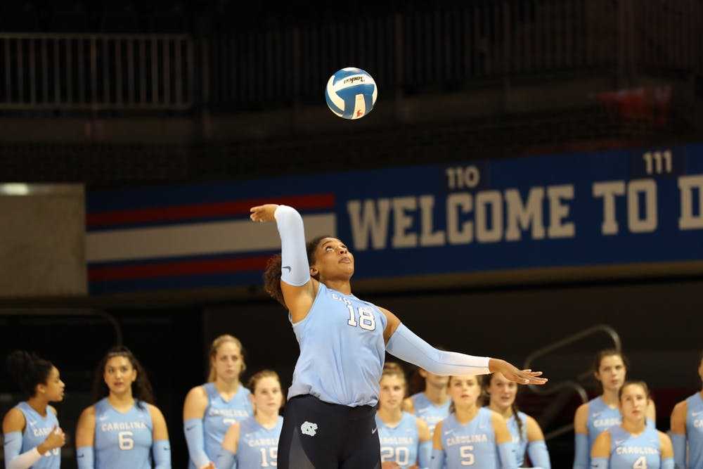 <p>UNC Graduate Outside Hitter Nia Parker-Robinson (18) serves the ball during warmups before the Tar Heels' Aug. 28 matchup with Southern Methodist University Volleyball in Dallas, Texas. Photo Courtesy of UNC Athletic Communications.</p>