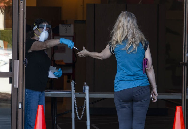 An early voting poll worker hands a pen to a voter at the Univesity Mall polling site on Thursday, Oct. 22, 2020.