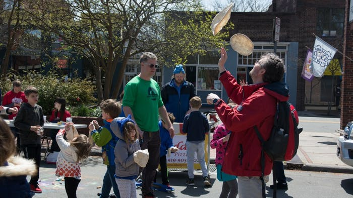 Attendees of the Carrboro Open Streets Festival toss pizza dough into the air among many other recreational activities on Weaver St. on Sunday, April 8, 2018.
