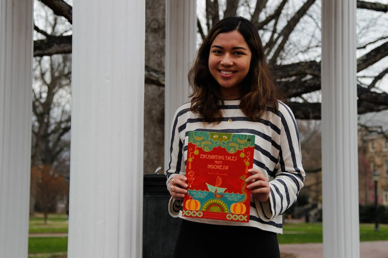 "Andari Deswandhy, a first-year global studies major, poses for a portrait at the Old Well with her book, Enchanting Tales from Indonesia, on Feb. 26, 2020.  Deswandhy says, ""I'm passionate about bringing different cultures together and helping people find similarities in our differences.""."