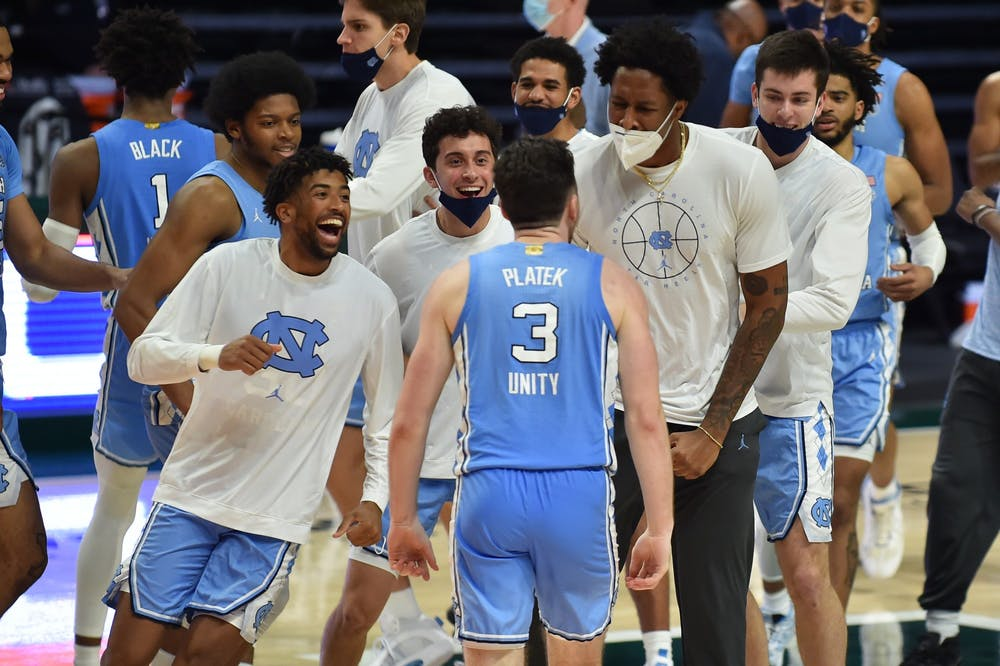 UNC men's basketball team cheers for senior guard Andrew Platek after his shot secured the Tar Heel's victory over the Miami Hurricanes during a game on Tuesday, Jan. 5, 2021. UNC beat Miami 67-65.  Photo courtesy of Maggie Bolton and Jeffrey Ridley.