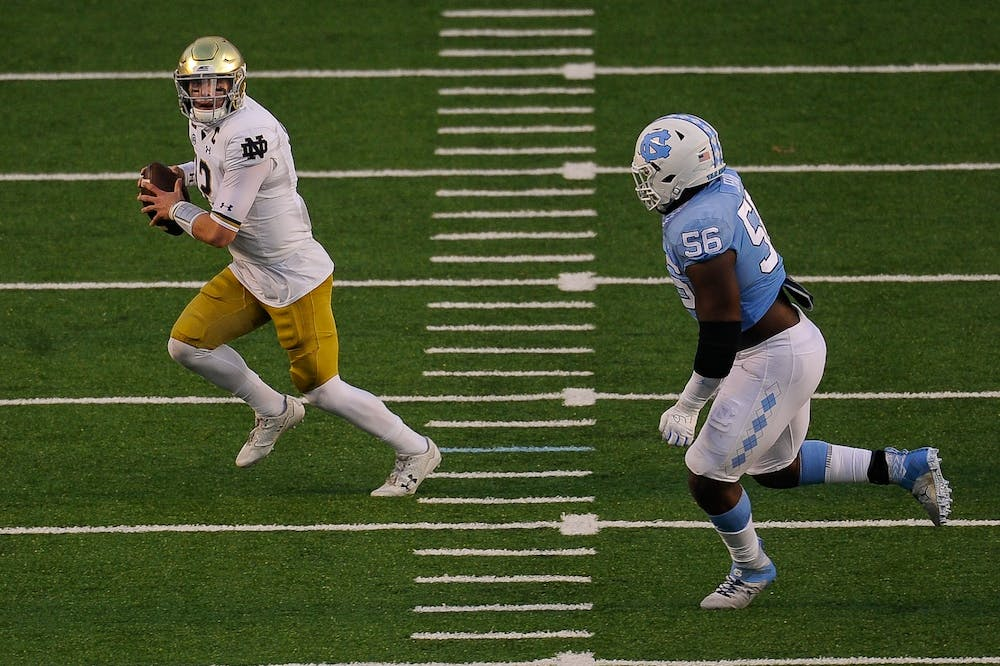 Notre Dame's graduate quarterback Ian Book (12) runs the ball downfield in Kenan Memorial Stadium during a game against UNC on Friday, Nov. 27, 2020.