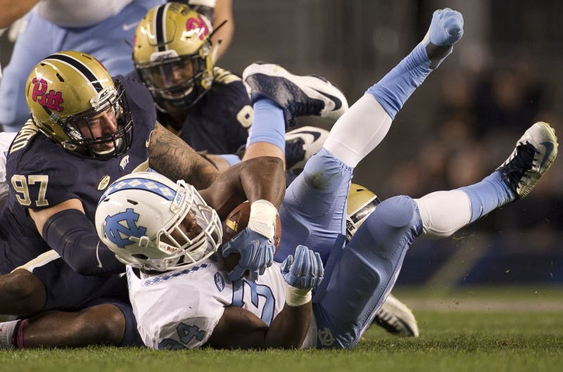 North Carolina tailback Elijah Hood (34) picks up 7 yards in the first quarter before losing a shoe and being stopped by Pittsburgh's Mark Scarpinato (97) on Thursday, Oct. 29, 2015, at Heinz Field in Pittsburgh. (Robert Willett/Raleigh News & Observer/TNS)
