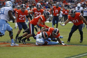 Virginia defensive players tackle sophomore wide receiver Rontavius Groves (4) during the game on Saturday at Scott Stadium. UNC lost to Virginia 21-31. It's the Tar Heels' fourth conference loss and sixth loss overall this season.