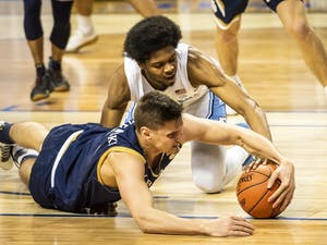 Notre Dame's Nate Laszewski (14) and Carolina's Kerwin Walton (24) battle for a loose ball on Wednesday, March 10, 2021 in Greensboro, N.C. Photo courtesy of Andrew Dye/Winston-Salem Journal.