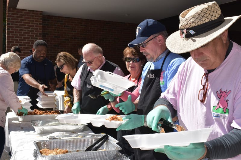 Employees from the Chapel Hill branch of Coldwell Banker Howard Perry and Walston prepare plates of barbecue for their annual Pig Out for the Cure fundraiser. The proceeds of the event, held with their Pittsboro branch, go to Lineberger Comprehensive Cancer Center.