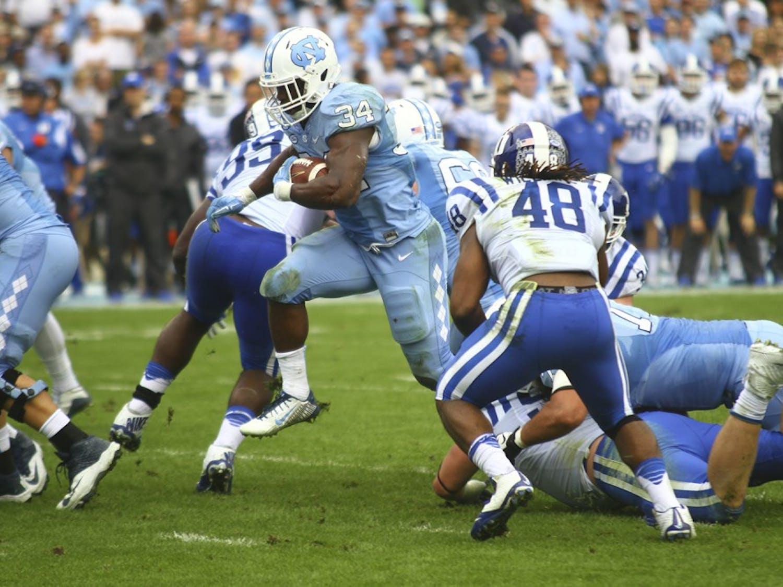 UNC running back Elijah Hood (34) breaks through Duke defenders during last year's matchup between the two teams.