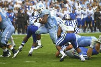 UNC running back Elijah Hood (34) breaks through Duke defenders during last year's matchup between the two teams.