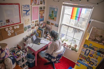Sophomore SamLevi Sizemore completes his German homework in his Chapel Hill apartment on Thursday, Sept. 10, 2020. As a studio art and English double major, Sizemore has filled his workspace with posters, plants and flags to make his apartment feel like home.