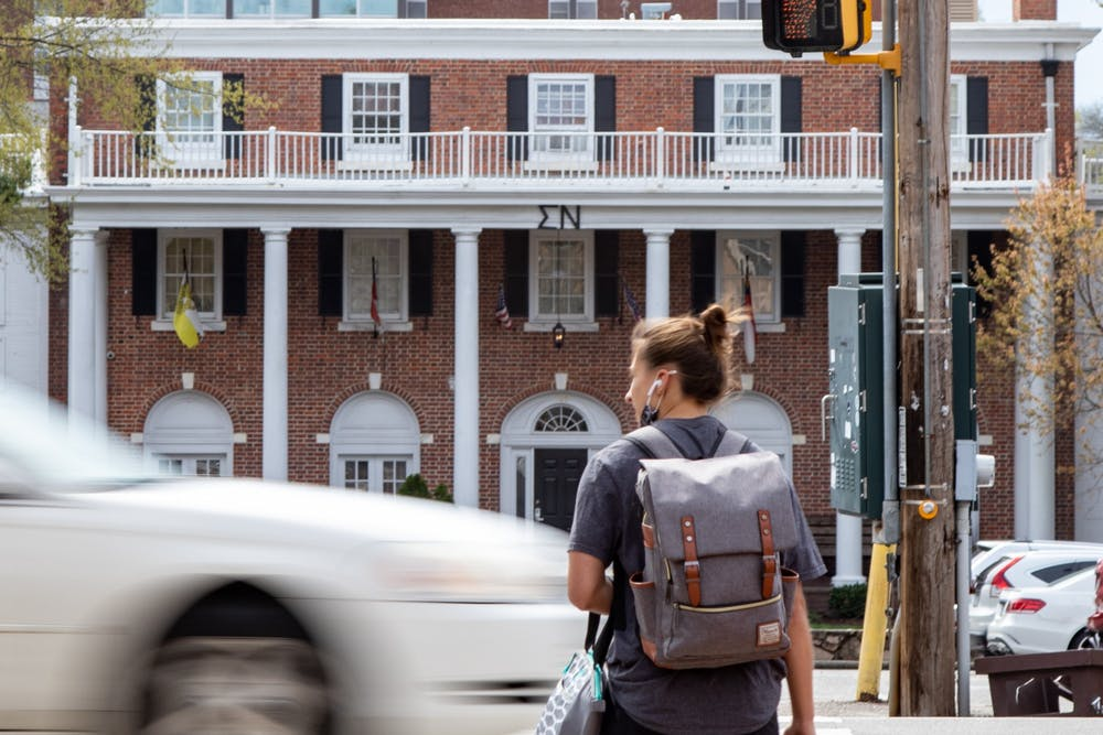 A woman crosses Columbia St in front of Fraternity Court on March 28, 2021.