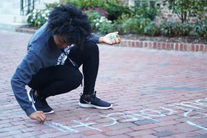 Dorothy Colon, a sophomore psychology major, chalks the sidewalk behind South Building with information about the UNC Boycott and Silent Sam.