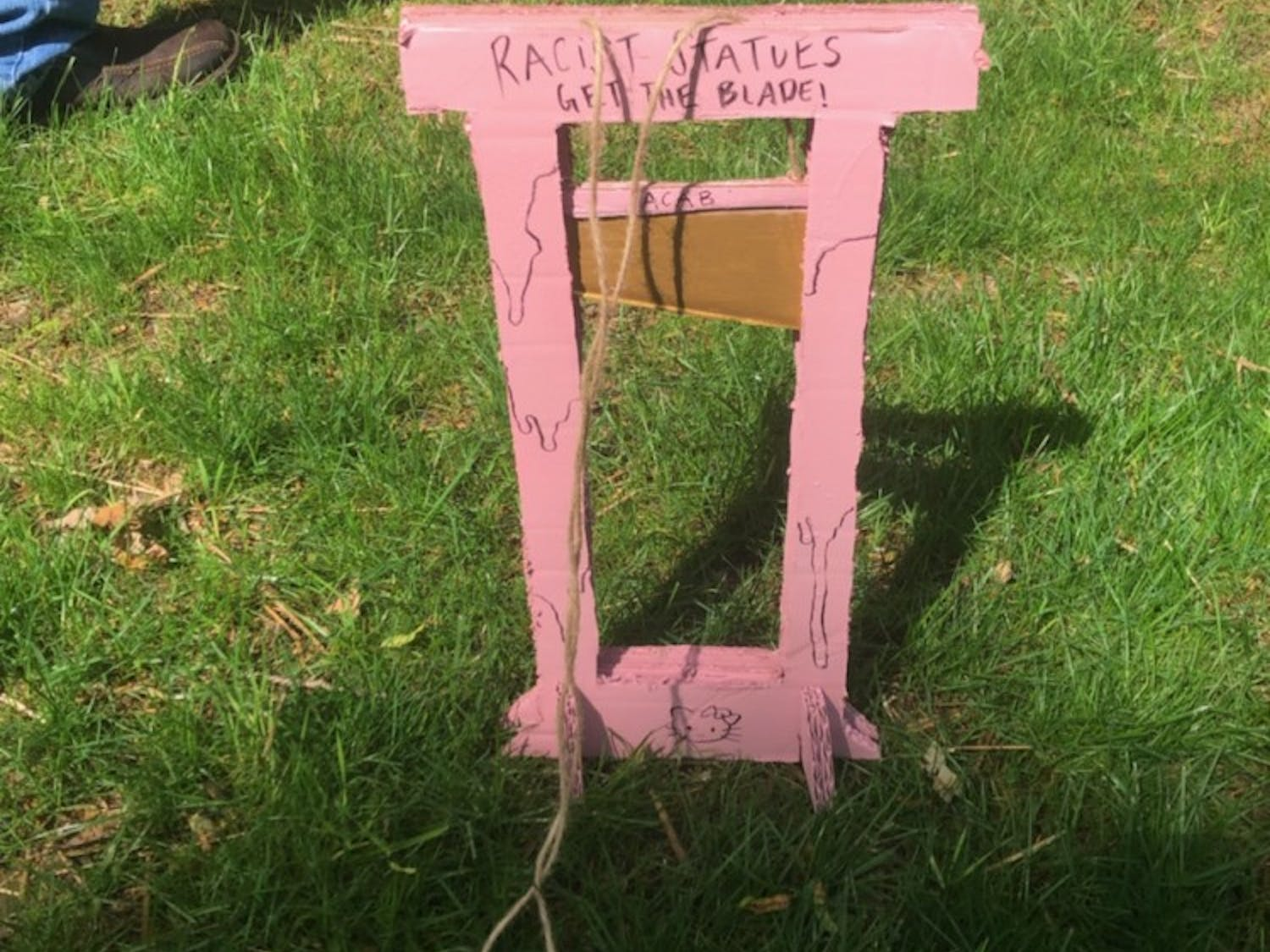 """Anti-Confederates put a small cardboard guillotine on McCorkle Place that said """"Racist Statues Get the Blade."""""""