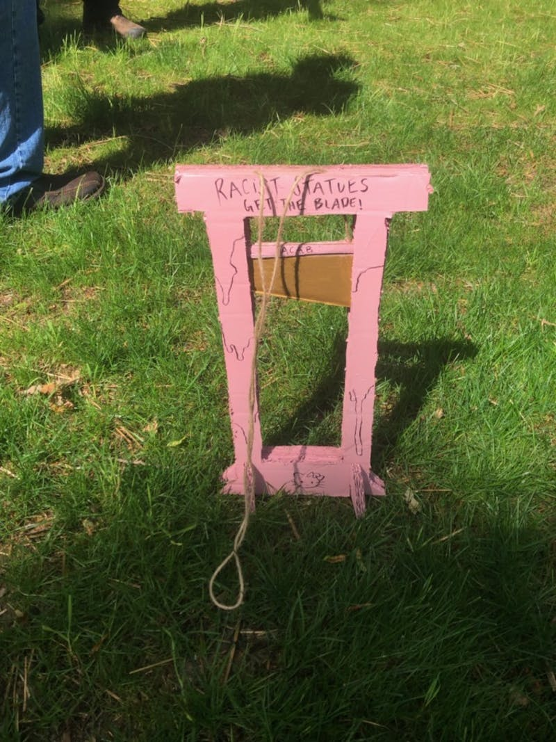 "Anti-Confederates put a small cardboard guillotine on McCorkle Place that said ""Racist Statues Get the Blade."""