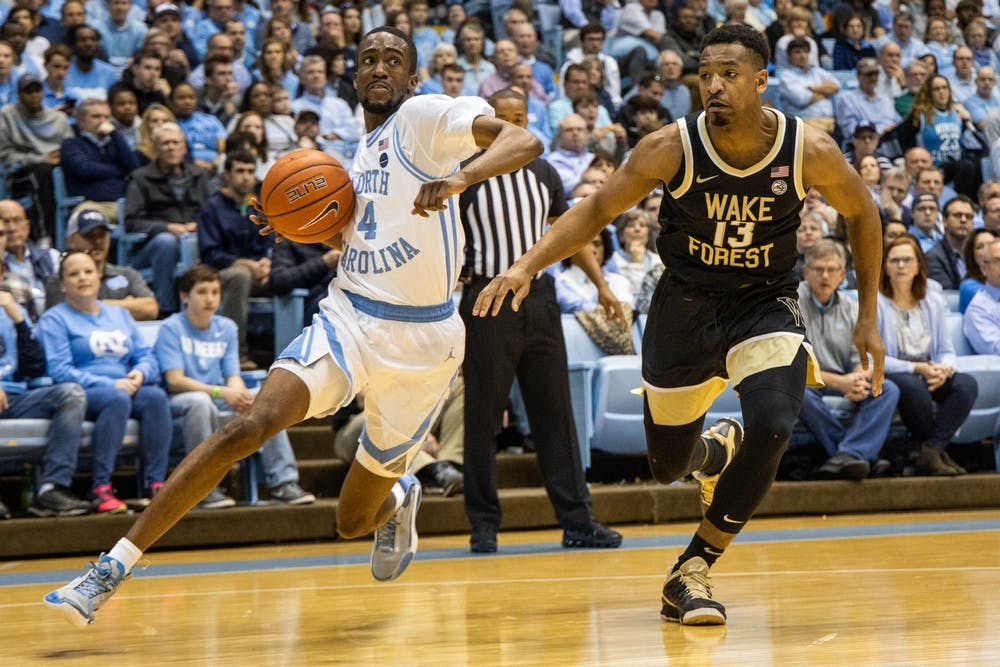 UNC senior guard Brandon Robinson (4) dribbles past Wake Forest senior guard Andrien White (13) in the Smith Center on Tuesday, March 3, 2020. The Tar Heels beat the Demon Deacons 93-83.