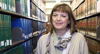 Martha Svoboda stands in the law library.